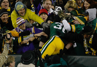 GREEN BAY, WI - NOVEMBER 14: John Kuhn #30 of the Green Bay Packers celebrates scoring a touchdown with a Lambeau Leap as he jumps in the stands during the game against the Minnesota Vikings at Lambeau Field on November 14, 2011 in Green Bay, Wisconsin. T