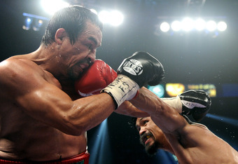 Juan Manuel Marquez is on the receiving end of a Manny Pacquiao left.  The decision was close, but correct!
