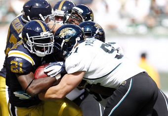 EAST RUTHERFORD, NJ - SEPTEMBER 18:  Paul Posluszny #51 of the Jacksonville Jaguars tackles LaDainian Tomlinson #21 of the New York Jets during their game at MetLife Stadium on September 18, 2011 in East Rutherford, New Jersey.  (Photo by Jeff Zelevansky/