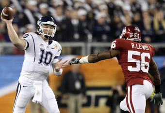 GLENDALE, AZ - JANUARY 01:  Zach Frazer #10 of the Connecticut Huskies attempts to throw the ball over Ronnell Lewis #56 of the Oklahoma Sooners in the first half in the Tostitos Fiesta Bowl at the Universtity of Phoenix Stadium on January 1, 2011 in Glen