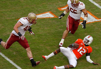 MIAMI GARDENS, FL - NOVEMBER 25:  Jacory Harris #12 of the Miami Hurricanes slides under a tackle during a game against the Boston College Eagles at Sun Life Stadium on November 25, 2011 in Miami Gardens, Florida.  (Photo by Mike Ehrmann/Getty Images)