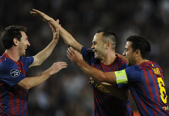 BARCELONA, SPAIN - OCTOBER 19:  Andres Iniesta of FC Barcelona (C) celebrates with his teammates Lionel Messi (L) and Xavi Hernandez after scoring the opening goal during the UEFA Champions League Group H match between FC Barcelona and FC Viktoria Plzen a