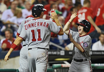 PHILADELPHIA, PA - SEPTEMBER 22: Michael Morse #38 and Ryan Zimmerman #11 of the Washington Nationals high five the bat boy after Morse hit a three run home run in the eighth inning against the Philadelphia Phillies at Citizens Bank Park on September 22,