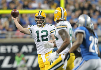 DETROIT, MI - NOVEMBER 24:  Aaron Rodgers #12 of the Green Bay Packers roles out to pass during the game against the Detroit Lions at Ford Field on November 24, 2011 in Detroit, Michigan.  The Packers defeated the Lions 27-15.  (Photo by Leon Halip/Getty