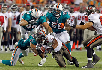 TAMPA, FL - AUGUST 27:  Running back Mossis Madu #32 of the Tampa Bay Buccaneers is tackled by defenders Tyrone Culver #29, Ryan Baker #90 and Robert Rose #56 of the Miami Dolphins during a preseason game at Raymond James Stadium on August 27, 2011 in Tam