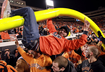STILLWATER, OK - DECEMBER 03:  Oklahoma State Cowboys fans hang on the goal post after a 44-10 win against the Oklahoma Sooners at Boone Pickens Stadium on December 3, 2011 in Stillwater, Oklahoma.  (Photo by Ronald Martinez/Getty Images)
