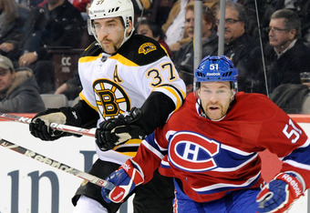 MONTREAL, CANADA - NOVEMBER 21:  Patrice Bergeron #37 of the Boston Bruins and David Desharnais #51 of the Montreal Canadiens battle for position during the NHL game at the Bell Centre on November 21, 2011 in Montreal, Quebec, Canada.  (Photo by Richard W