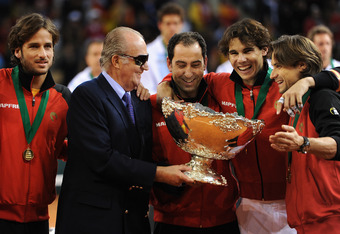 SEVILLE, SPAIN - DECEMBER 04:  King Juan Carlos (2nd L) of Spain holds the Davis Cup trophy with team captain Albert Costa (C), Rafael Nadal (2nd R), David Ferrer (R) and Feliciano Lopez during the third and last day of the final Davis Cup match between S