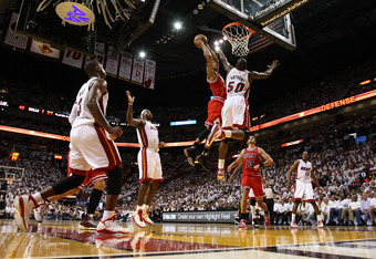 MIAMI, FL - MAY 24:  Derrick Rose #1 of the Chicago Bulls dunks on Joel Anthony #50 of the Miami Heat as LeBron James #6 of the Heat looks on in the first half of Game Four of the Eastern Conference Finals during the 2011 NBA Playoffs on May 24, 2011 at A