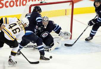 WINNIPEG, CANADA - DECEMBER 6: Ondrej Pavelec #31 of the Winnipeg Jets deflects a puck while Mark Stuart #5 watchs in a game against the Boston Bruins in NHL action at the MTS Centre on December 6, 2011 in Winnipeg, Manitoba, Canada. (Photo by Marianne He