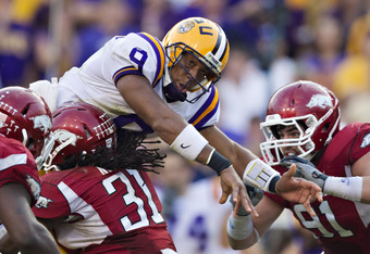 BATON ROUGE, LA - NOVEMBER 25:   Quarterback Jordan Jefferson #9 of the LSU Tigers is hit by Jerico Nelson #31of the Arkansas Razorbacks after throwing a pass at Tiger Stadium on November 25, 2011 in Baton Rouge, Louisiana.  The Tigers defeated the Razorb