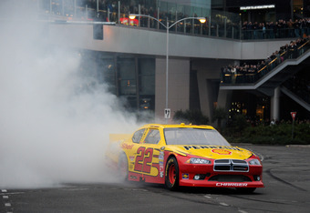 LAS VEGAS, NV - DECEMBER 01:  Kurt Busch, driver of the #22 Shell/Pennzoil Dodge, does a burnout during the NASCAR Victory Lap in front of the Wynn Las Vegas on Las Vegas Boulevard on December 1, 2011 in Las Vegas, Nevada.  (Photo by Ethan Miller/Getty Im