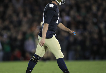 SOUTH BEND, IN - OCTOBER 22: Dayne Crist #10 of the Notre Dame Fighting Irish walks off of the field after fumbling the snap leading to a University of Southern California Trojans touchdown at Notre Dame Stadium on October 22, 2011 in South Bend, Indiana.