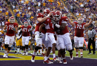 BATON ROUGE, LA - NOVEMBER 25:  (C) Wide receiver Jarius Wright #4 of the Arkansas Razorbacks celebrates with teammates after scoring on a 13-yard touchdown catch in the second quarter against the LSU Tigers at Tiger Stadium on November 25, 2011 in Baton