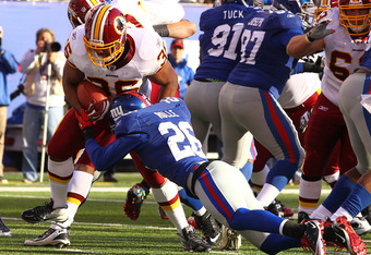 EAST RUTHERFORD, NJ - DECEMBER 18:  Darrel Young #36 of the Washington Redskins scores a touchdown as  Antrel Rolle #26 of the New York Giants misses the tackle during their game at MetLife Stadium on December 18, 2011 in East Rutherford, New Jersey.  (Ph