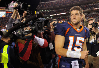 DENVER, CO - DECEMBER 18:  Quarterback Tim Tebow #15 of the Denver Broncos is the focus of the cameras as he leave the field after the game against the New England Patriots at Sports Authority Field at Mile High on December 18, 2011 in Denver, Colorado. T