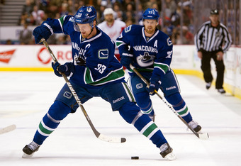 VANCOUVER, CANADA - DECEMBER 21: Henrik Sedin #33 of the Vancouver Canucks makes a drop pass to his brother and teammate Daniel Sedin #22 during the first period in NHL action against the Detroit Red Wings on December 21, 2011 at Rogers Arena in Vancouver