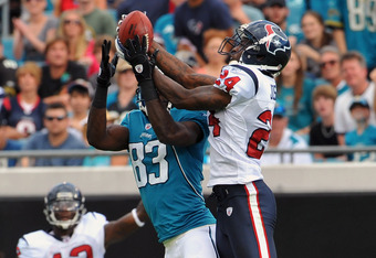 JACKSONVILLE, FL - NOVEMBER 27:  Cornerback Johnathan Joseph #24 of the the Houston Texans intercepts a pass intended for wide receiver Jason Hill #83 of the Jacksonville Jaguars November 27, 2011 at EverBank Field in Jacksonville, Florida. The Texans won