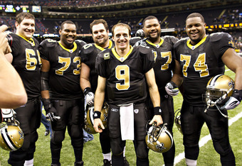 NEW ORLEANS, LA - DECEMBER 26:   Quarterback Drew Brees #9 and the offensive line of the New Orleans Saints pose after the game for a photo after Brees threw a nine-yard touchdown pass to running back Darren Sproles #43 and broke the single-season passing