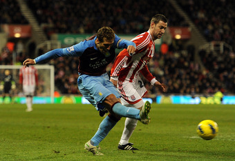 STOKE ON TRENT, ENGLAND - DECEMBER 26: Stiliyan Petrov of Aston Villa shoots at goal under pressure from Rory Delap of Stoke City during the Barclays Premier League match between Stoke City and Aston Villa at Britannia Stadium on December 26, 2011 in Stok