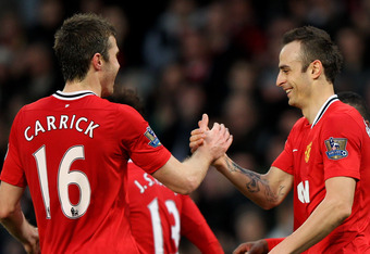 MANCHESTER, ENGLAND - DECEMBER 26:  Dimitar Berbatov of Manchester United celebrates scoring with team mate Michael Carrick (L) during the Barclays Premier League match between Manchester United and Wigan Athletic at Old Trafford on December 26, 2011 in M