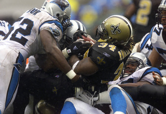 14 Oct 2001: Ricky Williams #34 of the New Orleans Saints gets tackled by Kris Jenkins #77 and Kory Minor #52 of the Carolina Panthers during the game at Ericsson Stadium in Charlotte, North Carolina. The Saints won 27-25. DIGITAL IMAGE. Mandatory Credit: