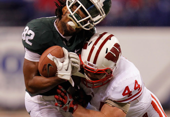 INDIANAPOLIS, IN - DECEMBER 03:  Keshawn Martin #82 of the Michigan State Spartans loses his helmet as he is hit by Chris Borland #44 of the Wisconsin Badgers during the third quarter of the Big 10 Conference Championship Game at Lucas Oil Stadium on Dece