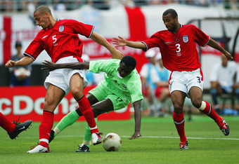OSAKA - JUNE 12:  Julius Aghahowa of Nigeria is closed down by Rio Ferdinand and Ashley Cole of England during the Group F match of the World Cup Group Stageplayed at the Osaka-Nagai Stadium, Osaka, Japan on June 12, 2002. The match ended in a 1-1 draw. (