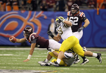 NEW ORLEANS, LA - JANUARY 03:  Logan Thomas #3 of the Virginia Tech Hokies attempts to reach for extra yardage as he is tackeled by Ryan Van Bergen #53 and Mike Martin #68 of the Michigan Wolverines during the Allstate Sugar Bowl at Mercedes-Benz Superdom