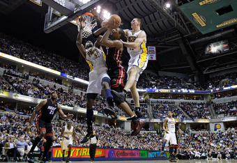 INDIANAPOLIS - FEBRUARY 15:  Chris Bosh #1 of the Miami Heat shoots the ball while defended by Roy Hibbert #55 and Tyler Hansbrough #50  of the Indiana Pacers during the NBA game at Conseco Fieldhouse on February 15, 2011 in Indianapolis, Indiana.   The H