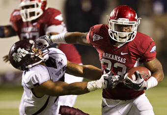 LITTLE ROCK, AR - NOVEMBER 19:   Dennis Johnson #33 of the Arkansas Razorbacks stiff arms Wade Bonner #7 of the Mississippi State Bulldogs at War Memorial Stadium on November 19, 2011 in Little Rock, Arkansas.  The Razorbacks defeated the Bulldogs  44 to