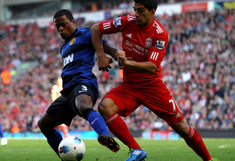 LIVERPOOL, ENGLAND - OCTOBER 15:  Luis Suarez of Liverpool tussles for posesssion with Patrice Evra of Manchester United during the Barclays Premier League match between Liverpool and Manchester United at Anfield on October 15, 2011 in Liverpool, England.