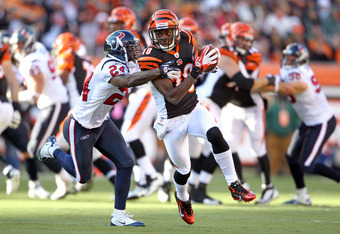 CINCINNATI, OH - DECEMBER 11:  A.J. Green #18 of the Cincinnati Bengals runs with the ball while defended by Brandon Harris #26 of the Houston Texans during the NFL game at Paul Brown Stadium on December 11, 2011 in Cincinnati, Ohio.  (Photo by Andy Lyons