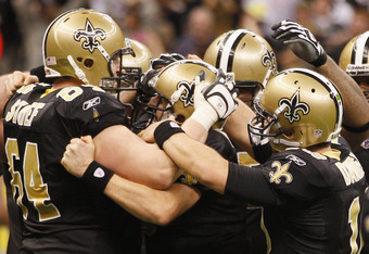 NEW ORLEANS, LA - DECEMBER 26:  Quarterback Drew Brees #9 of the New Orleans Saints is surrounded by his team after Brees throws a nine-yard touchdown pass to running back Darren Sproles #43 and breaks the single-season passing record in the fourth quarte