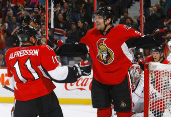 OTTAWA, ON - OCTOBER 14:  Milan Michalek #9 of the Ottawa Senators celebrates a goal with teammate Daniel Alfredsson #11 against Cam Ward #30 of the Carolina Hurricanes during a game at Scotiabank Place on October 14, 2010 in Ottawa, Ontario, Canada.  (Ph