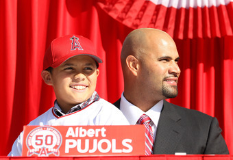 ANAHEIM, CA - DECEMBER 10:  Albert Pujols sits with son  Albert Jr. at a public press conference introducing newly signed Los Angeles Angels of Anaheim  players Pujols and C.J. Wilson at Angel Stadium on December 10, 2011 in Anaheim, California.  (Photo b