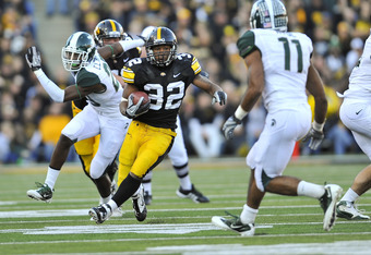 IOWA CITY, IA - OCTOBER 30:  Running back Adam Robinson #32 of the University of Iowa Hawkeyes rushes for yards past safety Marcu Hyde #11 of the Michigan State Spartans during the second half of play at Kinnick Stadium on October 30, 2010 in Iowa City, I