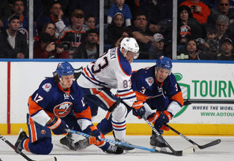 UNIONDALE, NY - DECEMBER 31: Ales Hemsky #83 of the Edmonton Oilers tries to move the puck around Matt Martin #17 (L) and Travis Hamonic #3 (R) of the New York Islanders at the Nassau Veterans Memorial Coliseum on December 31, 2011 in Uniondale, New York.