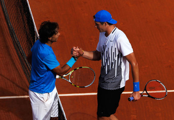 PARIS, FRANCE - MAY 24:  Rafael Nadal (L) of Spain shakes hands at the net with John Isner of USA after their men's singles round one match on day three of the French Open at Roland Garros on May 24, 2011 in Paris, France.  (Photo by Matthew Stockman/Gett