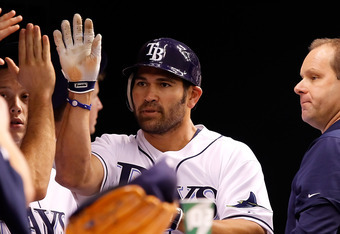 ST. PETERSBURG - OCTOBER 03:  Designated hitter Johnny Damon #22 of the Tampa Bay Rays is congratuled after scoring against the Texas Rangers during Game Three of the American League Division Series at Tropicana Field on October 3, 2011 in St. Petersburg,