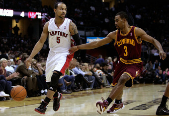 CLEVELAND, OH - DECEMBER 26:  Jerryd Bayless #5 of the Toronto Raptors handles the ball against Ramon Sessions #3 of the Cleveland Cavaliers during the season opener at Quicken Loans Arena on December 26, 2011 in Cleveland, Ohio. NOTE TO USER: User expres