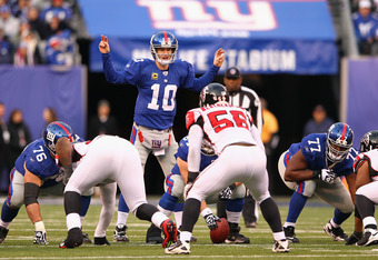 EAST RUTHERFORD, NJ - JANUARY 08:  Eli Manning #10 of the New York Giants gestures as he steps up to the line of scrimmage against the Atlanta Falcons during their NFC Wild Card Playoff game at MetLife Stadium on January 8, 2012 in East Rutherford, New Je