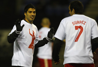 WIGAN, ENGLAND - DECEMBER 21:  Luis Suarez (L) looks towards Jose Enrique (R) of Liverpool as the teams warm up ahead of the Barclays Premier League match between Wigan Athletic and Liverpool at the DW Stadium on December 21, 2011 in Wigan, England.  (Pho