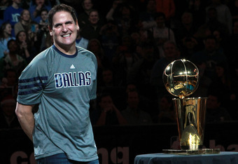 DALLAS, TX - DECEMBER 25:  Owner Mark Cuban of the Dallas Mavericks stands with the NBA trophy before a game against the Miami Heat on opening day of the NBA season at American Airlines Center on December 25, 2011 in Dallas, Texas.  NOTE TO USER: User exp
