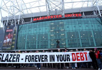 MANCHESTER, ENGLAND - JANUARY 23:  Manchester United fans, wearing green and gold scarves, protest against the Glazers, current owners of Manchester United before the Barclays Premier League match between Manchester United and Hull City at Old Trafford on