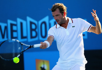 MELBOURNE, AUSTRALIA - JANUARY 19:  Julien Benneteau of France plays a forehand in his second round match against Gilles Simon of France during day four of the 2012 Australian Open at Melbourne Park on January 19, 2012 in Melbourne, Australia.  (Photo by