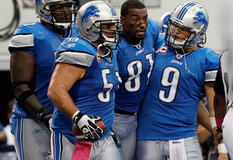 ARLINGTON, TX - OCTOBER 02:   Gosder Cherilus #77 of the Detroit Lions (L), Dominic Raiola #51 of the Detroit Lions (2nd  L) and  Matthew Stafford #9 of the Detroit Lions (R) assist  Calvin Johnson #81 of the Detroit Lions to the bench after scoring the g