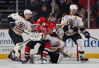 NEWARK, NJ - JANUARY 19: Dennis Seidenberg #44, goaltenderTim Thomas #30 and Zdeno Chara #33 of the Boston Bruins defend the net against Adam Henrique #14 of the New Jersey Devils at the Prudential Center on January 19, 2012 in Newark, New Jersey. The Bru