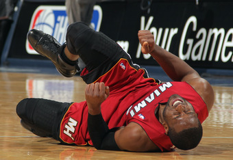 DENVER, CO - JANUARY 13:  Dwyane Wade #3 of the Miami Heat falls to the court with an injury in the fourth quarter against the Denver Nuggets at the Pepsi Center on January 13, 2012 in Denver, Colorado. Wade left the game after the injury as the Nuggets d