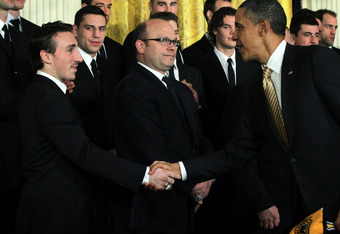 WASHINGTON, DC - JANUARY 23:  U.S. President Barack Obama (R) shakes hands with hockey player Brad Marchand (L) of the Boston Bruins as team general manager Peter Chiarelli (2nd L) looks on during a East Room event at the White House January 23, 2012 in W
